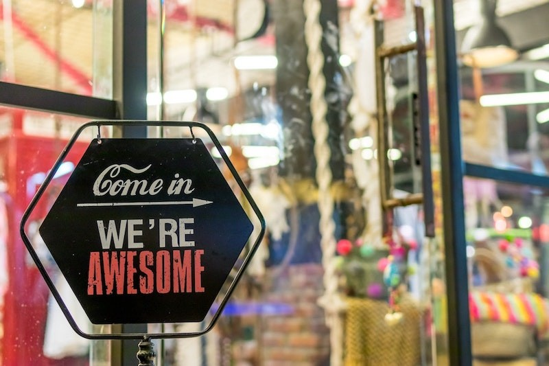 """Come In, We're Awesome"" sign in front of store."